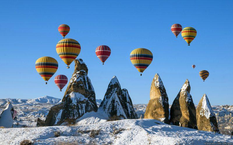 Globos de colores sobrevolando las montañas heladas
